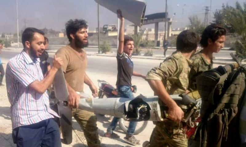 مدنيون وعسكريون يحملون حطام الطائرة في حي باب النيرب - الثلاثاء 2 آب (تويتر)