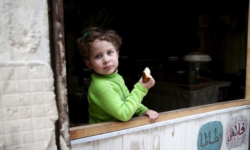 طفلة تتناول الخبز عند محلّ للمأكولات الشعبية في حي القابون في دمشق آذار 2016 (رويترز)