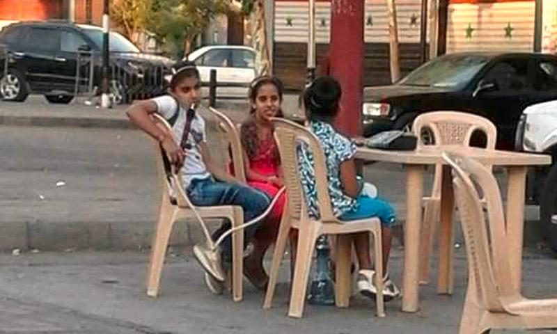 """استنكرت الصفحات الموالية للنظام السوري على موقع """"فيس بوك"""" خلال يومي عيد الأضحى الماضيين، عددًا من الصور التي ظهر فيها أطفال يشربون """"الأركيلة"""" في مقاهي دمشق. واعتبرت صفحة """"أخبار الهاون بدمشق"""" أن الظاهرة """"خطيرة"""" مشيرةً إلى أن """"خطر الأركيلة أكبر من خطر الدخان على الجسم""""، ودعت إلى مكافحة هذه الظاهرة """"برسم وزارة الشؤون الاجتماعية والسياحة. الصور نشرتها عشرات الصفحات الموالية للأسد، ولم تقتصر على """"أخبار الهاون بدمشق""""، تظهر أطفالًا (ذكور وإناث) لا تتجاوز أعمارهم 11 عامًا يتلذذون بنفخ دخان """"الأركيلة"""" في الهواء. سيل من التعليقات على الصور جاء في الصفحة، وكتب أحدهم """"للأسف هالشي منتشر بشكل كبير جدًا ومن الضروري إيجاد حل لهالأمر""""، واعتبر آخر أن المطاعم هي التي تروج لمثل هذه الأمور وقال """"اليوم عم اقرأ عروض المطاعم، بيكتبلك وجبة مع كولا وأركيلة بألفين وشوي، يعني كأنو الأركيلة صارت بدل قنينة المي"""". كثيرون عزوا المسؤولية للحكومة السورية وكتب أحدهم """"الحق كلو على الدولة اللي رخّصت الطرقات والأماكن العامة لأصحاب النفوس الضعيفه والجشعين اللي ما بيهمهم إلا الربح المادي"""". آخرون أجمعوا على أن """"المجتمع فاسد والدولة أكثر فسادًا والحرب خربت الدنيا، وبالتالي ضاعت سوريا وجيل المستقبل"""" بينما اعتبر بعضهم أنه """"بالكافيات والمطاعم المحترمة بيسأل أديش عمرك قبل ما يعطي الأركيلة، وإلا في عليها مخالفة بس أنا برأي هيك أعدات بالشارع لازم تلتغى لأنو ماعليها مراقبة ولامخالفة"""". أحد الموالين أخلى مسؤولية الحكومة بهذا الخصوص وكتب """"هي وظيفة الأهل وليس الحكومة، ومسؤولية المواطن يلي بيستقبل هيك حالات بالمقهى""""، وتساءل آخر """"العالم بفترة الحرب فلتت عالآخر ليش ما كنا نشوف هيك قصص قبل الأزمة؟"""". ظاهرة انتشار المقاهي لا تقتصر على دمشق، بل غزت بشكل لافت الأماكن العامة والمقاهي في كل من اللاذقية وطرطوس وبعض أحياء حلب الخاضعة لسيطرة النظام. وبين اتهامات وجهت إلى الحكومة وغيرها، يبقى الأطفال دون رقيب في ظاهرة تفشت بشكل واسع، وفق ما رصدت عنب بلدي على الصفحات الموالية للأسد، وعلى صفحات مهتمين شاركوها من تلك الصفحات."""