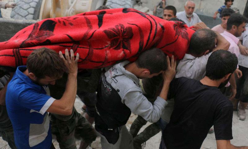 مواطنون يحملون جثمان أحد ضحايا القصف الجوي على حي المرجة في مدينة حلب- الجمعة 23 أيلول (AFP)