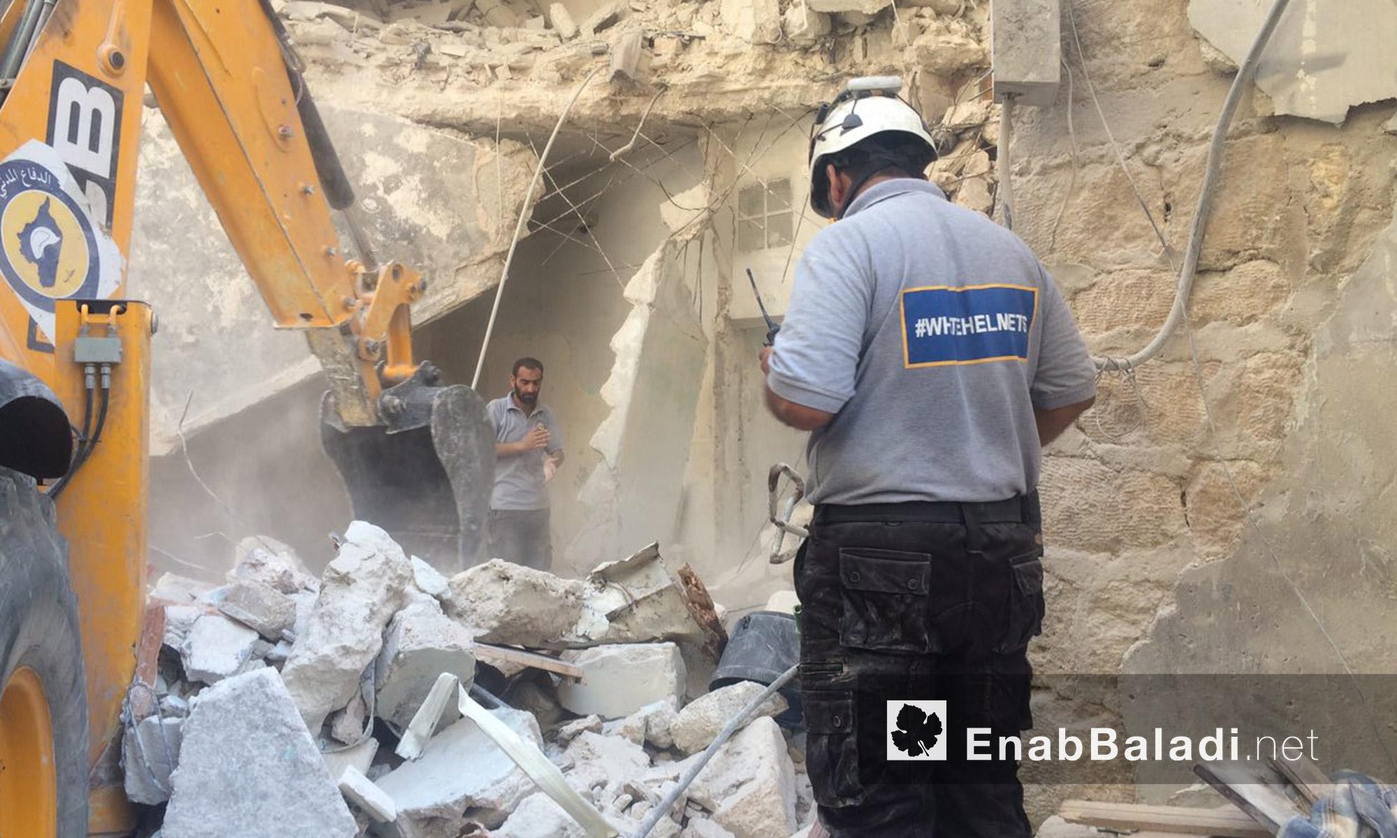 عنصران من الدفاع المدني بين آثار القصف على حي السكري في حلب - الاثنين 5 أيلول (عنب بلدي)