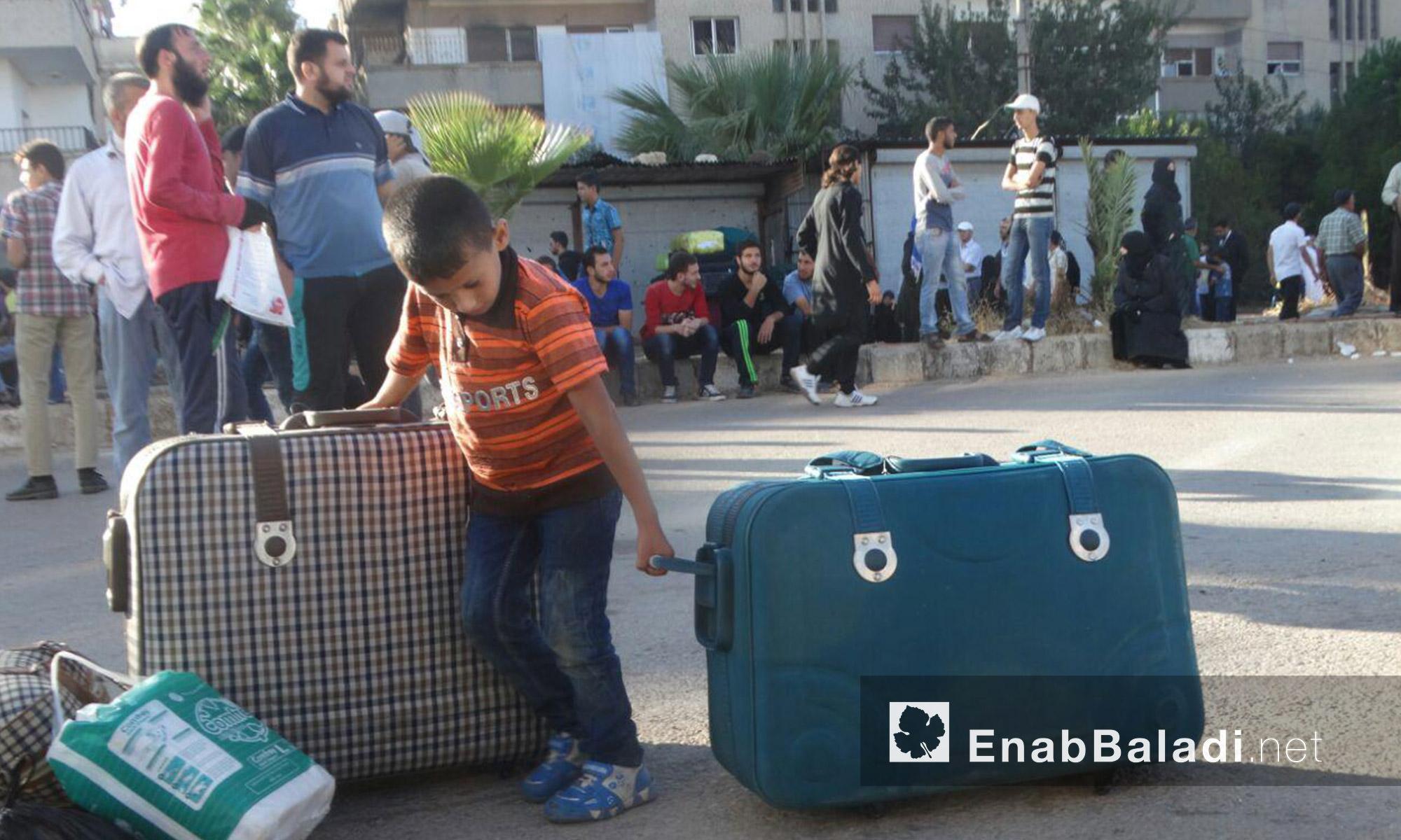 طفل يجهز حقائب عائلته قبل الخروج من الحي إلى ريف إدلب - الاثنين 19 أيلول (عنب بلدي)