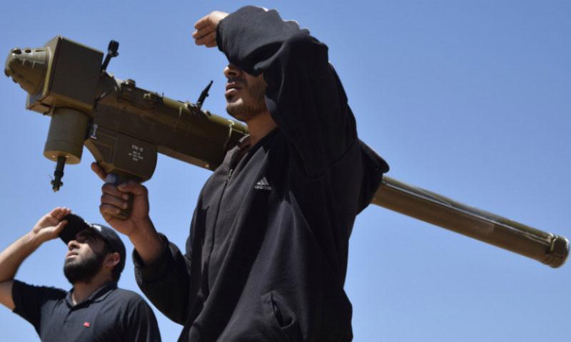 مقاتلو المعارضة يحملون صاروخ FN-6 في تيرمعلة بحمص 20 نيسان 2016 (AFP)
