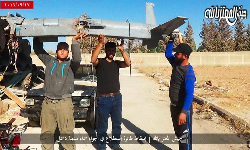 """مقاتلو """"جيش المعتز بالله"""" يحملون طائرة الاستطلاع في داعل - 27 أيلول (فيس بوك)"""