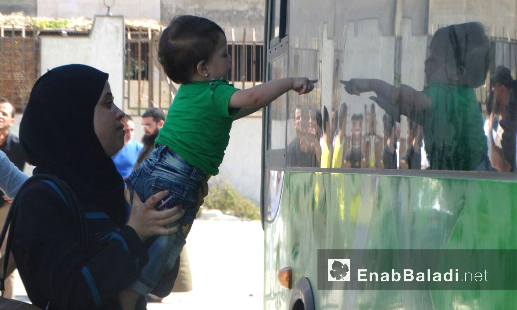 طفل يشير بإصبعه إلى المقاتلين داخل الباص في حي الوعر - الخميس 23 أيلول (عنب بلدي)