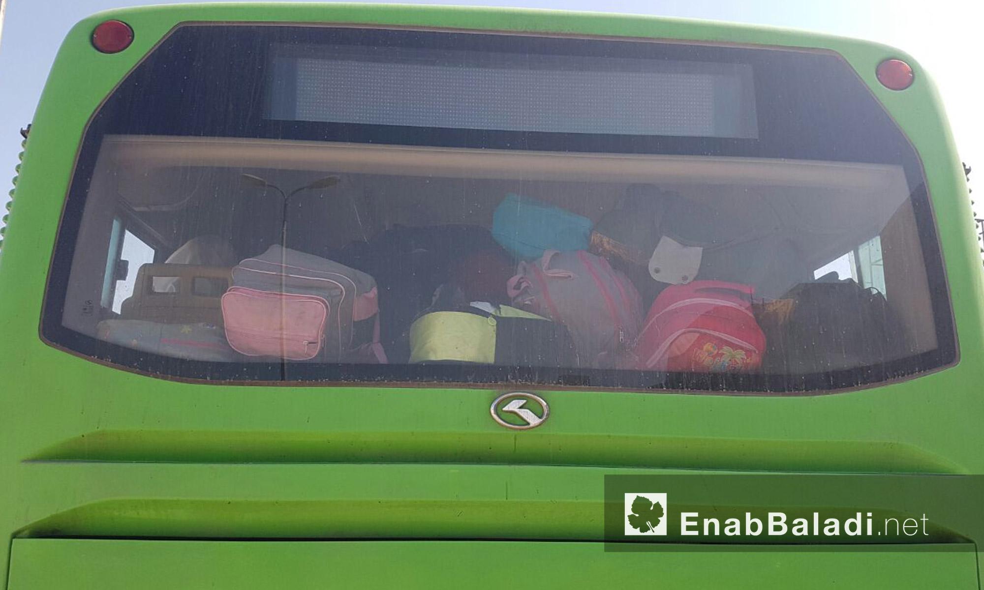 حقائب عائلات الوعر داخل الباص الأخضر قبل خروجهم إلى ريف حمص الشمالي - الخميس 23 أيلول (عنب بلدي)