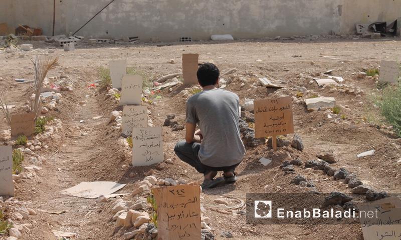 شاب يودّع مقبرة الشهداء في داريا - 26 آب 2016 (عنب بلدي)