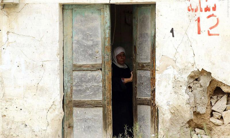 امرأة سورية تتفحص منزلها بعد العودة إليه في تدمر بريف حمص نيسان 2016 (AFP)