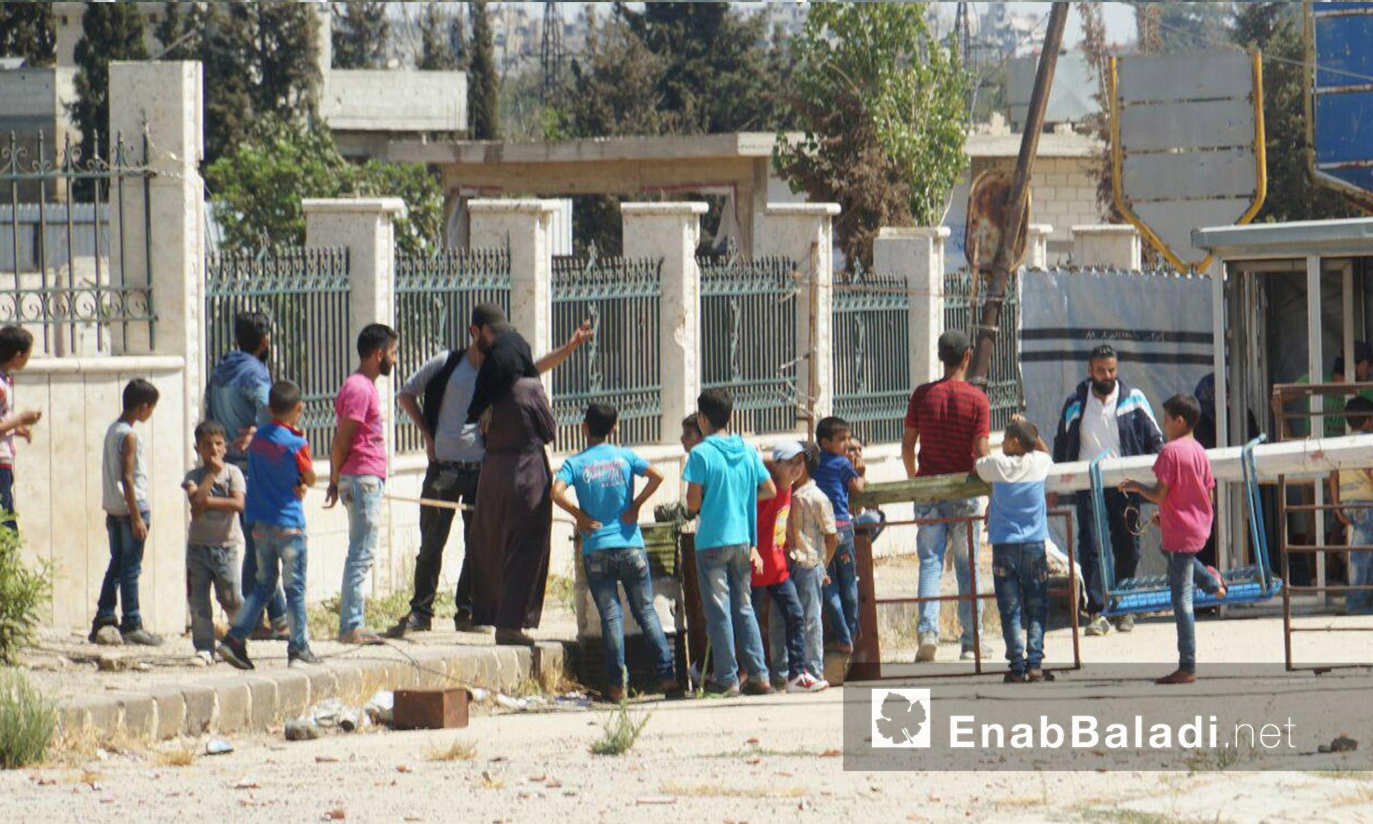 """أطفال ونساء قرب معبر """"دوار المهندسين"""" في حي الوعر بحمص - الثلاثاء 6 أيلول (عنب بلدي)"""