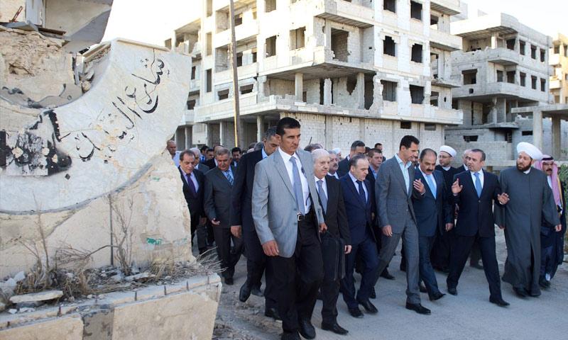 بشار الأسد مع عددٍ من المسؤولين وإلى جانبهم قاعدة تمثال الأسد دون رأسه (فيس بوك)