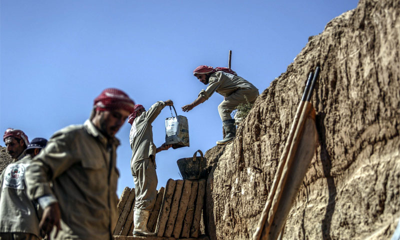 عمال يبنون قبور في مدينة دوما بريف دمشق (EPA)