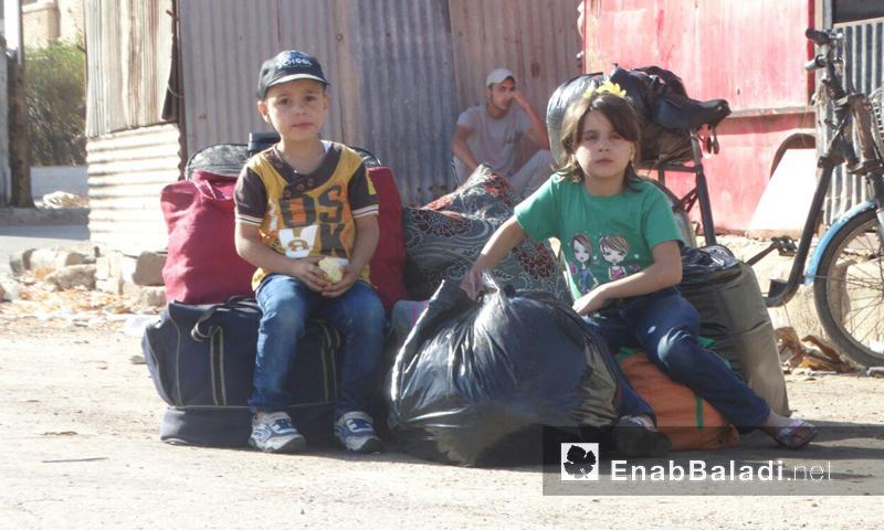 طفلان من حي الوعر ينتظران صعودهما الحافلات الخضراء باتجاه الريف الشمالي- الاثنين 26 أيلول (عنب بلدي)