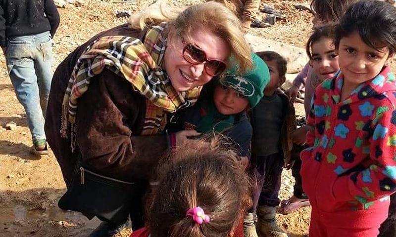 """السيدة راوية الأسود، مؤسسة منظمة """"سوريات عبر الحدود، مع عددٍ من الأطفال السوريين (فيس بوك)"""