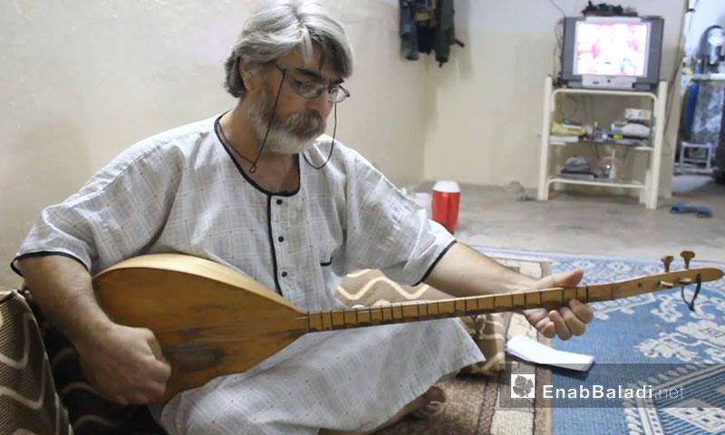 عادل مراد، مسرحي وشاعر كردي، يعزف على آلة الطنبورةى (عنب بلدي)