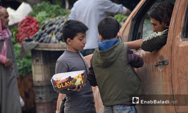 """طفلان يبيعان """"البسكويت"""" للمارة في مدينة حلب - تشرين الأول 2016 (عنب بلدي)"""