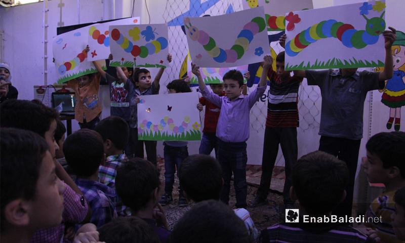 أطفال سوريون يعرضون رسوماتهم في مدينة دوما - تشرين الأول 2016 (عنب بلدي)
