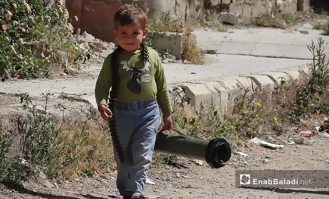 طفل سوري يحمل سلاحًا في مدينة درعا جنوب سوريا - تشرين الأول 2016 (عنب بلدي)