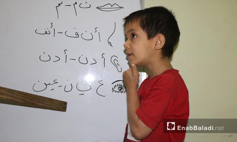 """طفل يتعلم أجزاء الجسم في مدرسة """"البيان"""" للصمّ والبكم في الغوطة الشرقية - تشرين الأول 2016 (عنب بلدي)"""