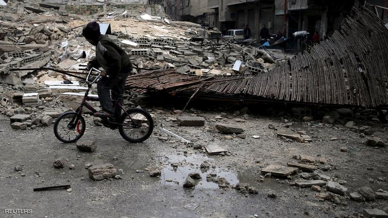 طفل يقود دراجته يبن الركام في دوما في الغوطة الشرقية - تشرين الثاني 2015 (بسام خبية/رويترز)