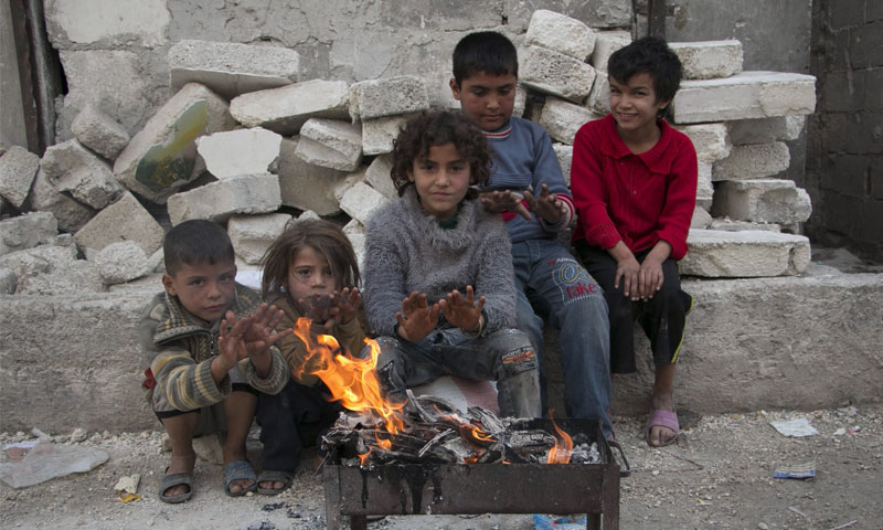 أطفال سوريين ينالون قسطًا من الدفء في إحدى المخيمات (انترنت)