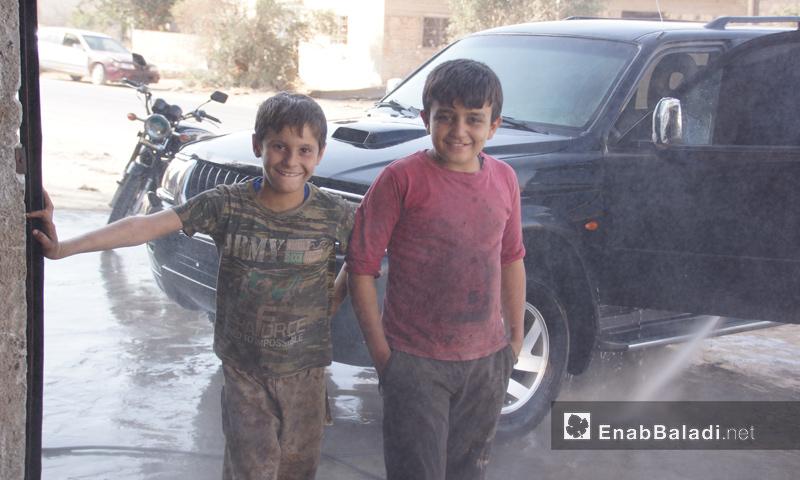 طفلان يعملان في مغسل للسيارات بريف إدلب - تشرين الأول 2016 (عنب بلدي)