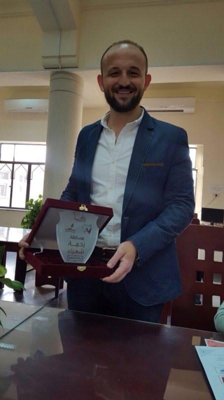 """الطالب السوري عمار يحيى يحمل درع جائزة """"زحمة شعراء"""" (فيس بوك)"""