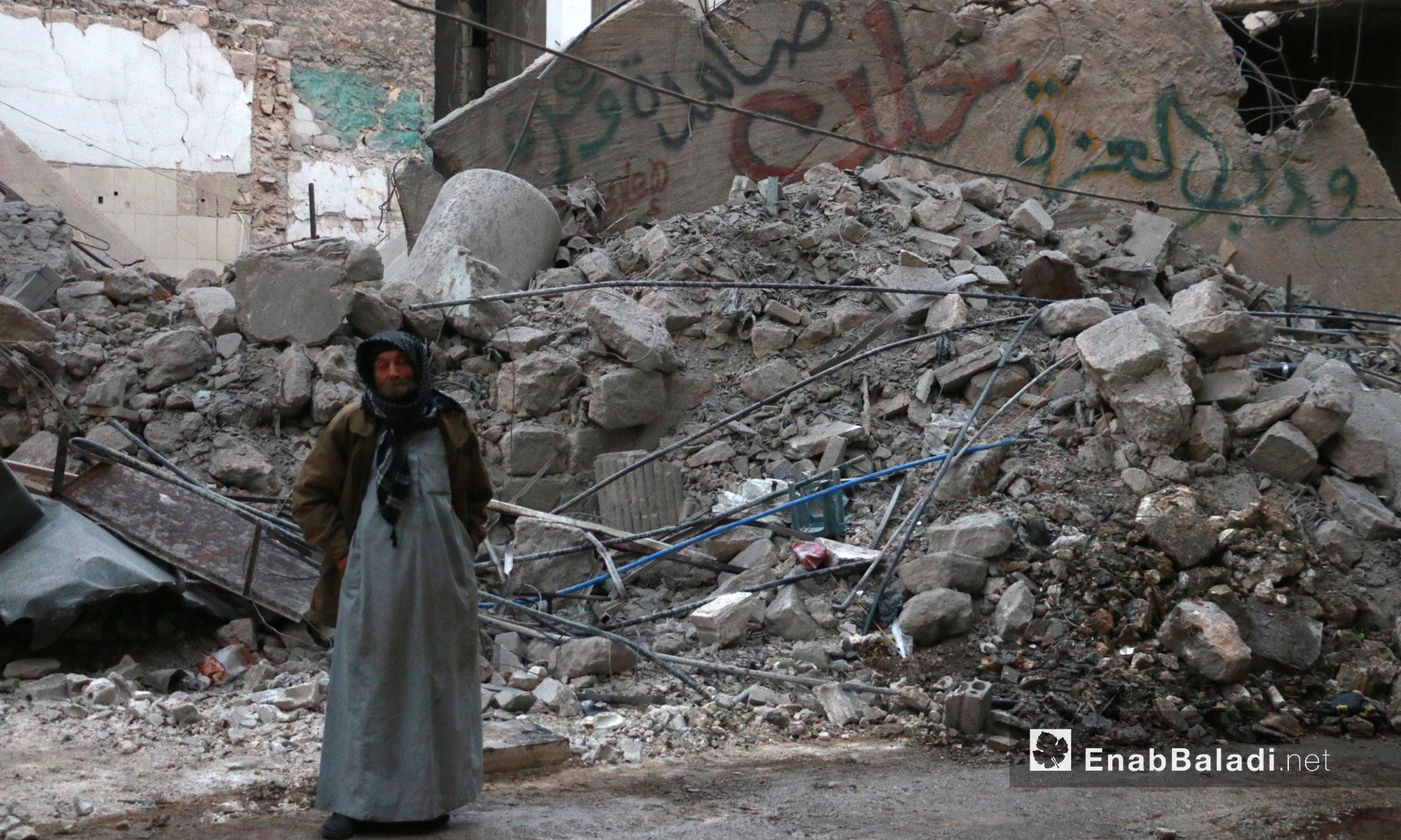 رجل كهل يقف إلى جانب ركام القصف وكتابات على جدار في حي الشعر بحلب - 17 تشرين الثاني 2016 (عنب بلدي)