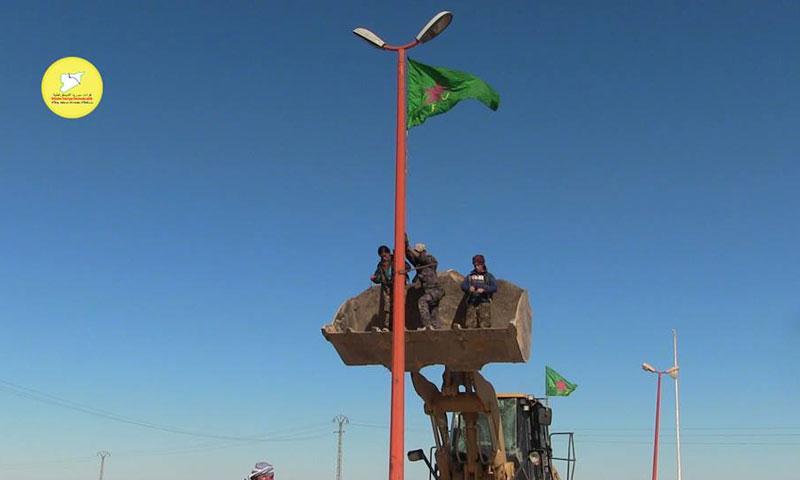 رفع علم وحدات حماية المرأة الكردية في قرية تل السمن شمال الرقة السبت 19 تشرين الثاني