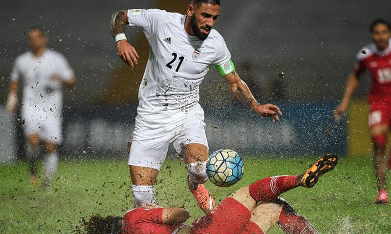 لاعب المنتخب السوري ينزلق أمام لاعب إيراني خلال المواجهة بين المنتخبين - 15 تشرين الثاني 2016 (AFP)