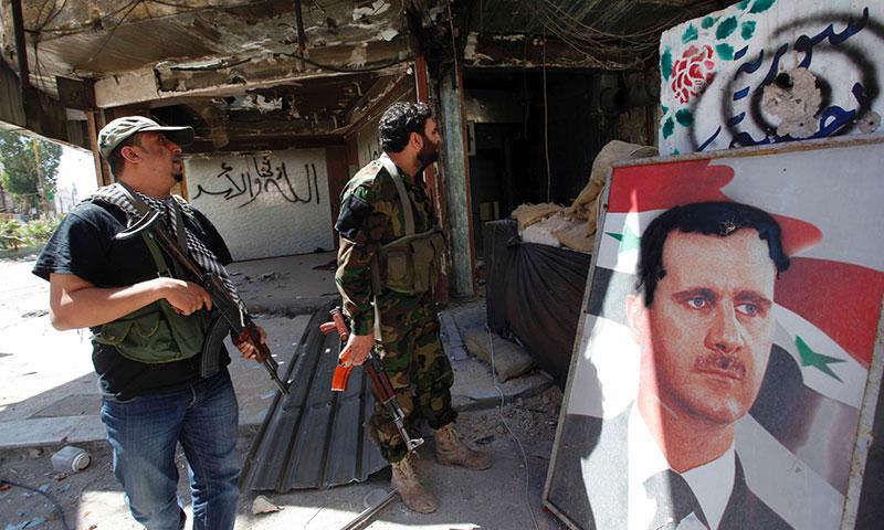 """أرشيفية- مقاتلون من ميليشيا """"الدفاع الوطني"""" في سوريا (تويتر)"""