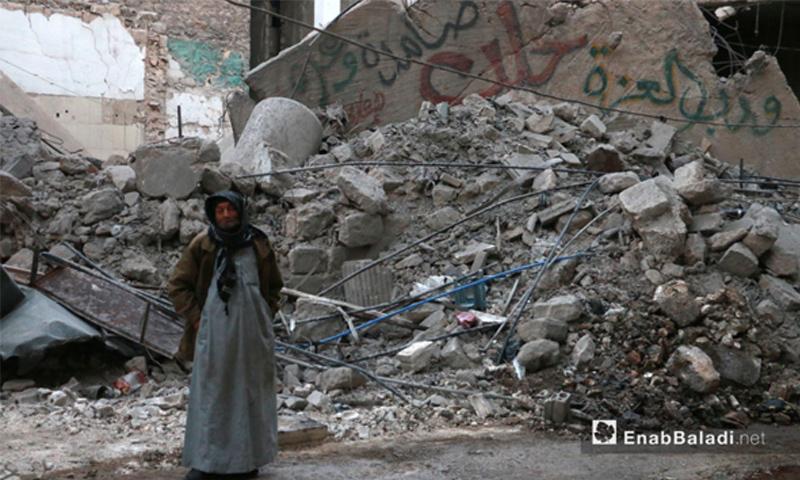 كهل يقف إلى جانب ركام القصف وكتابات على جدار في حي الشعار بحلب - 17 تشرين الثاني 2016 (أرشيف عنب بلدي)