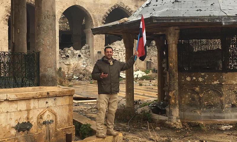 """مدير مكتب قناة """"العالم"""" الإيرانية في سوريا، حسين مرتضى، حاملًا علم النظام السوري، داخل الجامع الأموي الكبير في حلب- كانون الأول 2016 (فيس بوك)"""