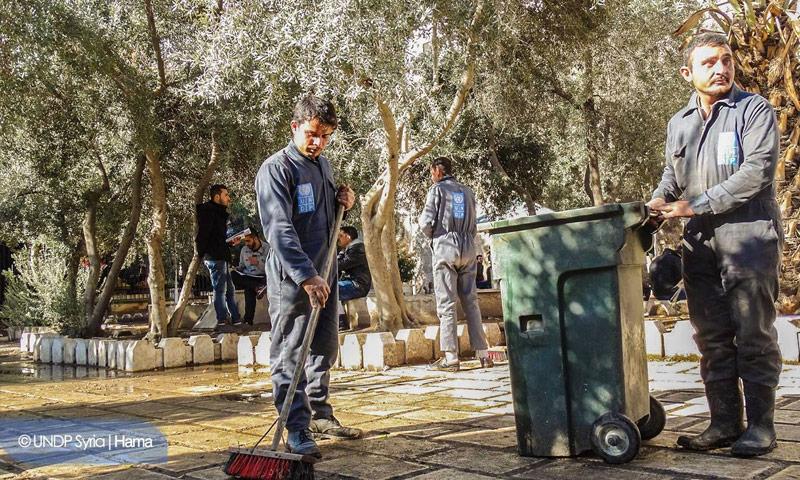 """""""إزالة النفايات المتراكمة في كلية الآداب بحماة لنشر التوعية بين الطلاب حول أهمية الحفاظ على بيئة نظيفة"""". (صفحة فيسبوك لبرنامج الأمم المتحدة الإنمائي)"""