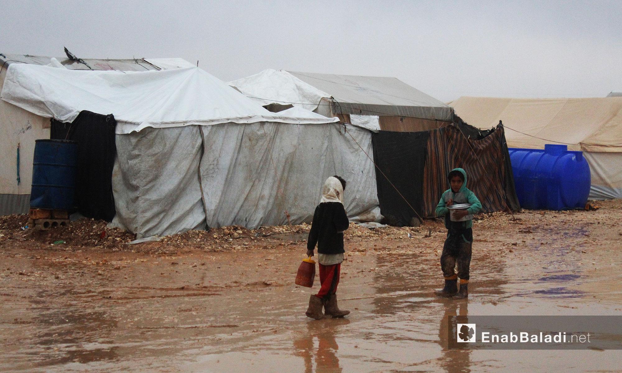 طفلان نازحان بعد توقف الأمطار في مخيم بريف حلب الشمالي - 1 كانون الأول 2016 (عنب بلدي)