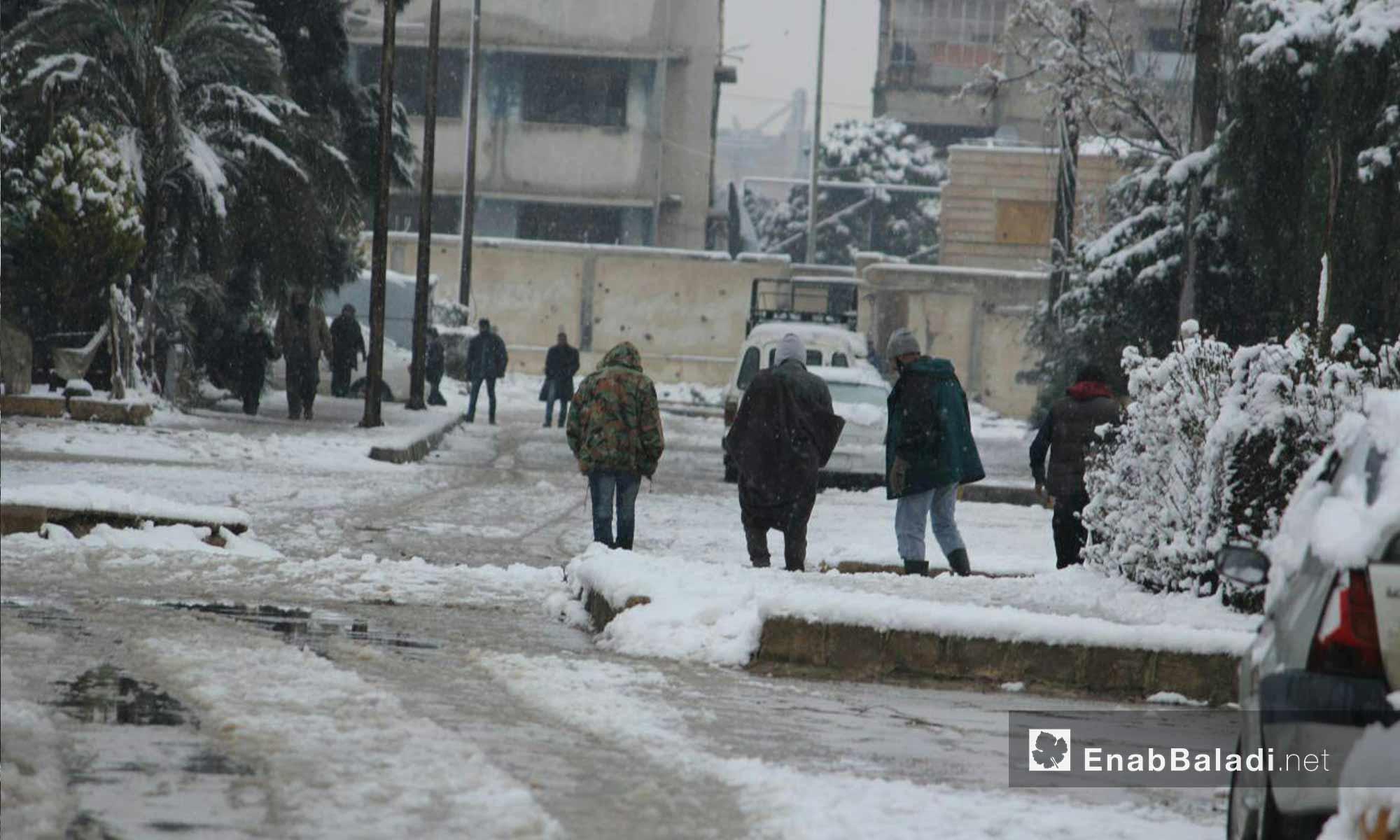 حركة الأهالي في حي الوعر أثناء تساقط الثلوج_18 كانون الأول_(عنب بلدي)