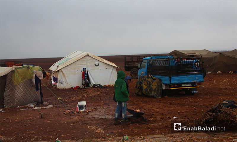 عائلة سورية توقد النار في مخيم بريف حلب الشمالي