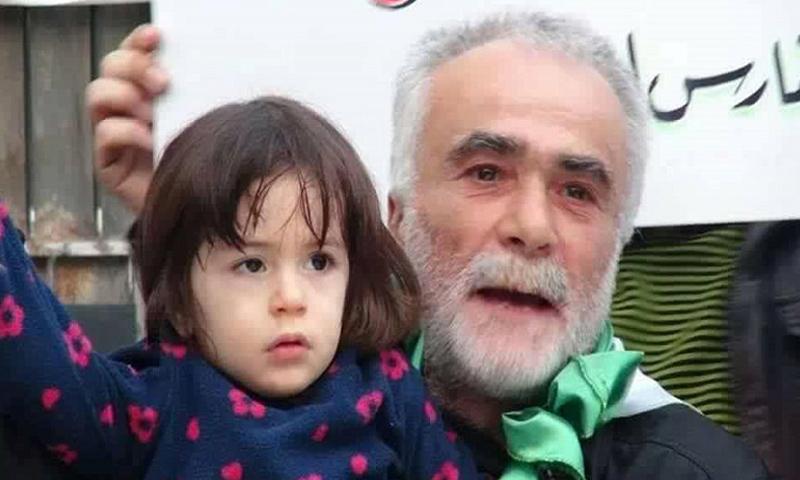 أبو ماجد كرمان حاملًا حفيدته في إحدى مظاهرات حلب (أرشيفية)
