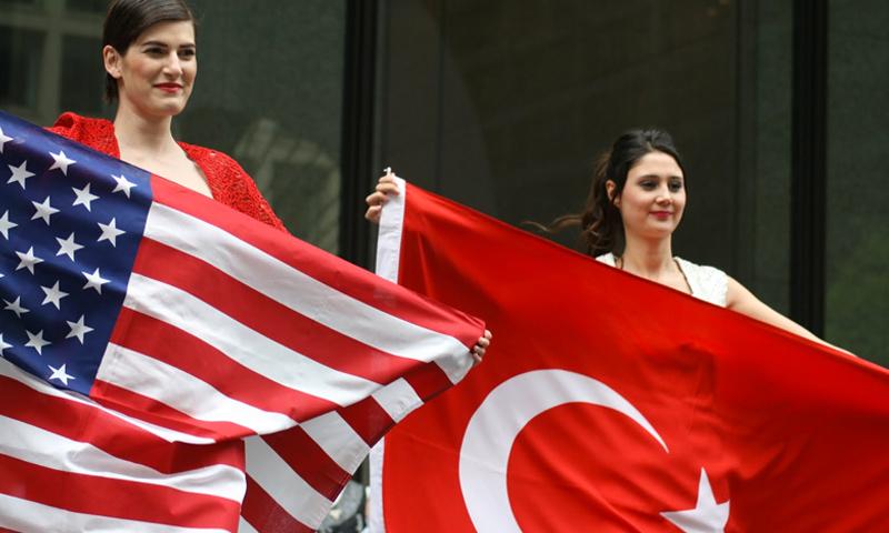 مواطنتان تركيتان ترفعان علمي تركيا والولايات المتحدة (إنترنت)