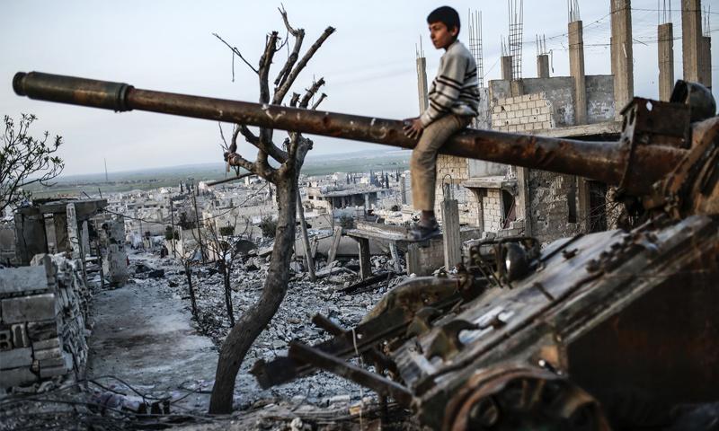 تعبيرية: طفل يجلس على مدفع دبابة في سوريا (إنترنت)