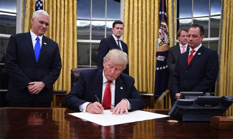 الرئيس الأمريكي دونالد ترامب يوقع قراراته الأولى في البيت الأبيض (إنترنت)