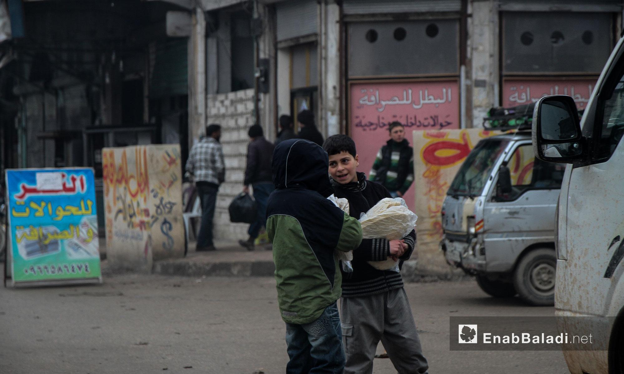 أطفال يحملون الخبز صباحًا في مدينة إدلب - 17 كانون الثاني (عنب بلدي)