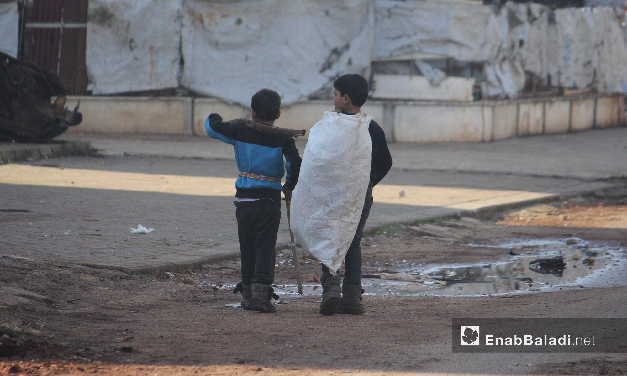 طفلان في طريقهما إلى عملهما في حي الوعر بمدينة حمص - 21 كانون الثاني 2017 (عنب بلدي)