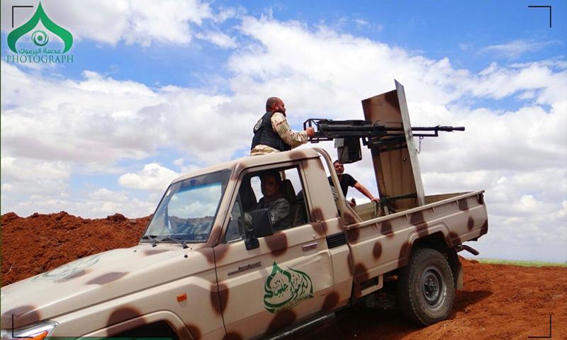 مقاتلون يعتلون سيارة تحمل رشاشًا تابعة لجيش اليرموك في درعا (جيش اليرموك)
