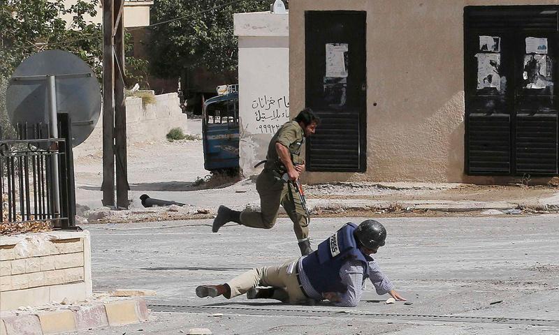"""مراسل وكالة """"AFP"""" ملقىً على الأرض إثر رصاصات قناص في معلولا بريف دمشق - 18 أيلول 2013 (عنب بلدي)"""