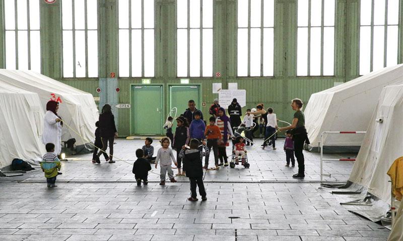 طفال لاجئين سوريين يلعبون بجانب الخيام في ملجأ للمهاجرين تابع لمطار تمبلهوف في برلين، ألمانيا - 9 تشرين الثاني 2015 ( REUTERS)