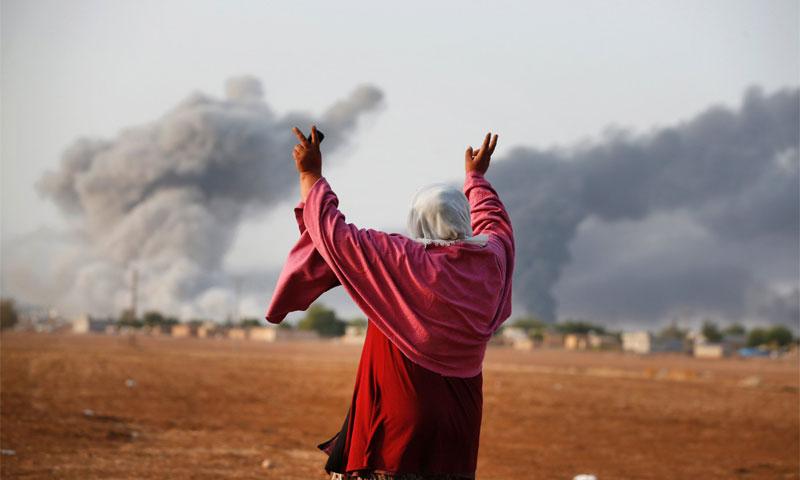 امرأة ترفع أصابع النصر إثر قصفٍ نفذّته مقاتلات أمريكية على مدينة كوباني على الحدود السورية- التركية 13 تشرين الأول 2014 (AP)