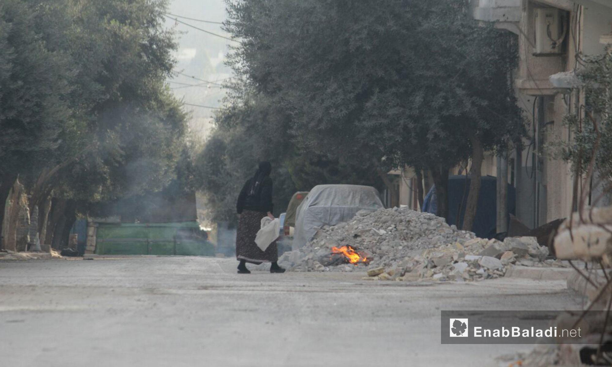 امرأة في حي الوعر في حمص تتخلص من القمامة بحرقها - 2 شباط 2017 (عنب بلدي)