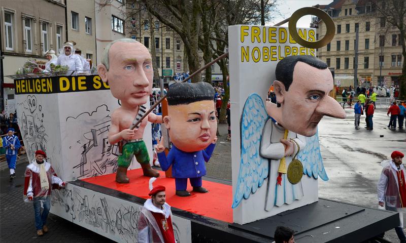 كرنفال يتضمن مجسمات لرئيس النظام السوري، بشار الأسد، والزعيم الكوري كيم جونغ، والرئيس الروسي، فلاديمير بوتين (AP)