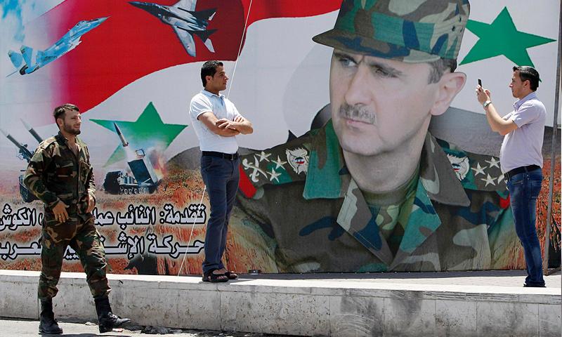 رجل يلتقط صورة بجانب لوحة لرئيس النظام السوري، بشار الأسد، في دمشق (رويترز)