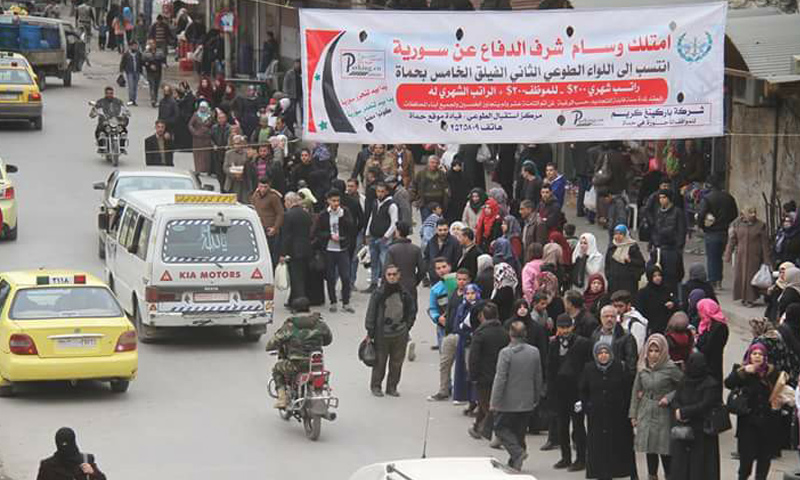 """لافتة طرقية وسط مدينة حماة تدعو للتطوع في """"الفيلق الخامس""""- 11 شباط 2017 (فيس بوك)"""